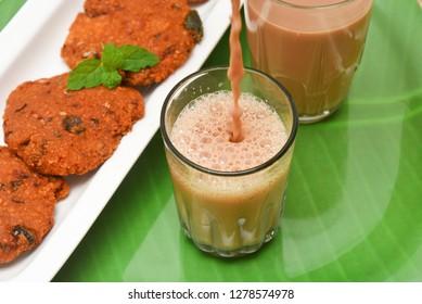 Pouring Indian milk tea or Chai  with Parippu vada Kerala Snacks popular deep fried hot and spicy tea time food. Traditional food for Ramadan, Onam, Vishu in tamil nadu, Street food of India.