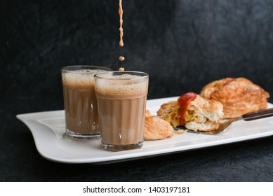 Pouring Indian milk tea in glass severed with chicken or meat puffs, pattie pastries, popular bakery snacks with tomato sauce or ketchup in Kerala India. food cut and being served using server.