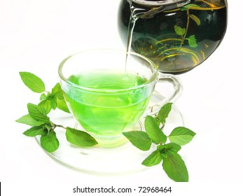 pouring into cup green herbal tea with fresh mint