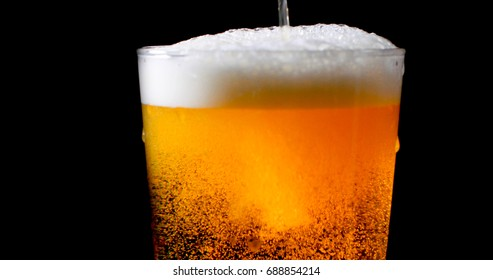 Pouring lager beer on a pint glass with black background