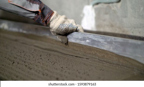 Pouring, laying concrete at the construction site using buckets of cement. Building, concrete work on the roof. Alignment of the concrete screed. Workers pour the solution on the roof. Leveling wet