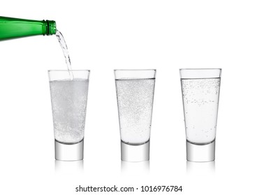 Pouring lemonade soda drink sparkling water from bottle to glass