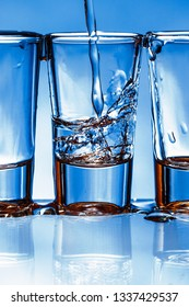 Pouring liquor into transparent vodka shot glass. Blue weekend party alcohol background.