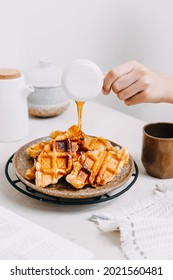 Pouring maple syrup into a plate of croffle. Mix of croissant and waffle which made using croissant dough molded in a waffle machine. Tea time situation in bright mood background.