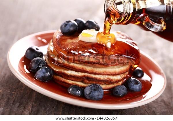 Nalévání javorového sirupu na stoh palačinek