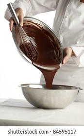 Pouring melted chocolate into a metal bowl