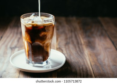 Pouring milk in an iced coffe in a tall glass with a straw on a rustic wooden table