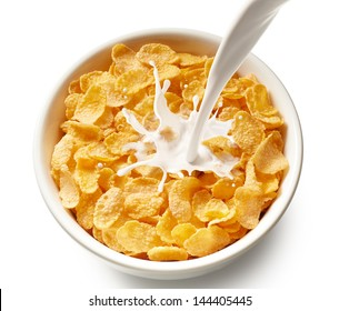 pouring milk into bowl of corn flakes, top view