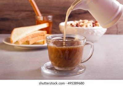 Pouring milk into coffee in a glass cup