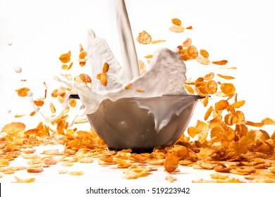 pouring milk into corn flakes creating  splash