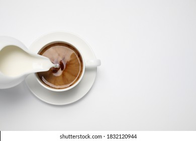 Pouring milk into cup of coffee on white background, top view