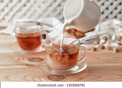 Pouring of milk into cup of tea on wooden table