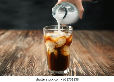 Pouring milk into glass of cold brew coffee on dark table