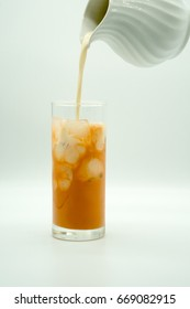 pouring milk into a glass of ice Thai Milk Tea isolated on white background