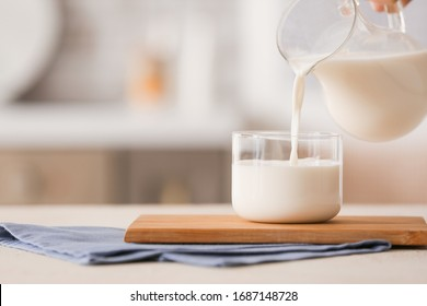 Pouring of milk into glass on table