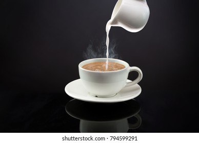 Pouring a milk in to a mug of hot coffee or tea on black background