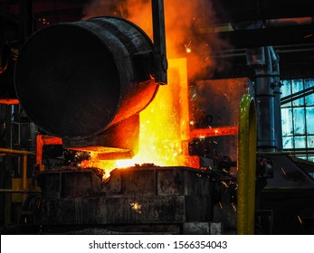 Pouring of molten ore with ladle and pouring into molds. mineral casting industry