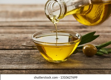 pouring oil from bottle into glass bowl, olive tree leaves and olive on wooden surface
