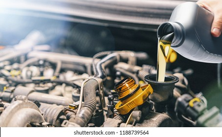 Pouring oil to car engine. Fresh motor oil poured during an oil change to a car.