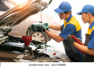 Pouring oil to car engine, Mechanic pouring oil into car at the repair garage