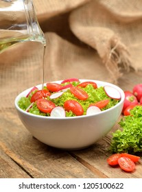 Pouring oil into green salad Lollo Biondo with tomatoes and radishes in a white bowl on wooden table, a pitcher of oil in the background - vertical photo
