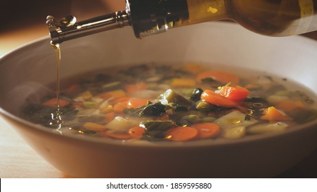 Pouring oil on minestrone soup. Vegetarian soup dish is on table. Vegetarian healthy meal for dinner. Ready vegetable meal for lunch, hot and cozy soup for dinner at home.