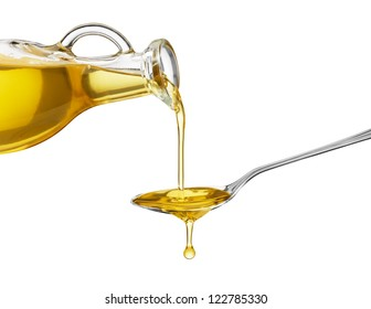 pouring oil on spoon from glass bottle