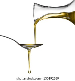 Pouring oil on spoon isolated on white