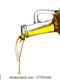 Pouring olive oil from glass bottle, isolated white background