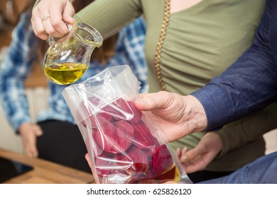 Pouring olive oil into plastic bag with beetroots and preparing for sous vide cooking. Two chefs cooking sous vide.