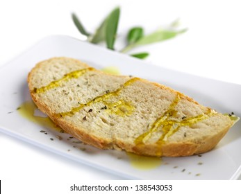 pouring olive oil on a slice of bread with oregano