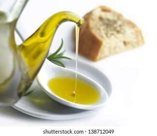 pouring olive oil on a spoon and a slice of bread with oregano