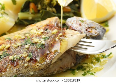 pouring olive oil on very fresh seabream fish grilled - traditional food from Portugal