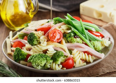 Pouring olive oil over delicious pasta salad
