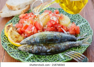 pouring olive oil in very fresh sardines cooked in sea salt - traditional food from Portugal