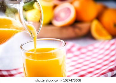 Pouring orange juice in to glass. Tropical fruits juice in glass with orange, lime and grep. Fresh orange nectar.