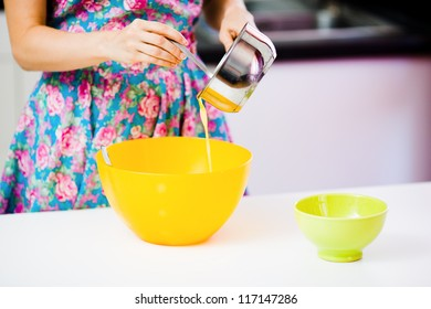 Pouring out melted butter from a metallic pot to an orange plastic bowl at homely kitchen