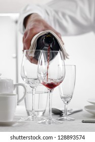 Pouring out red wine from a bottle in an elegant dining table setting at a restaurant or hotel