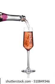 Pouring pink rose champagne from bottle to glass on white background with reflection