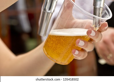 pouring a plastic glass of beer