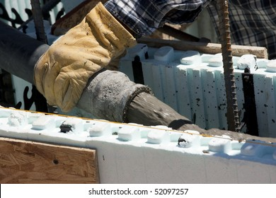 Pouring pumped concrete into foam forms at new house construction.