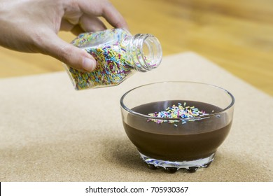 Pouring Rainbow Sprinkles On Chocolate Pudding