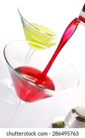 Pouring red beverage into a martini glass.