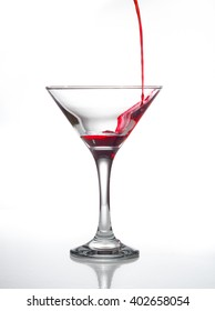 Pouring red and green alcoholic beverage in a cocktail glass isolated on white background