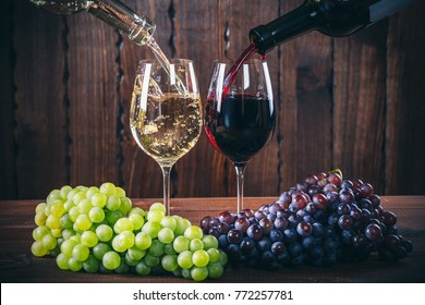 Pouring red and white wine into the  wine glasses with a bunch of red and white grapes against wooden background
