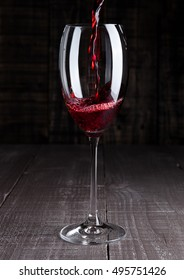 Pouring red wine from bottle to the glass on wooden board