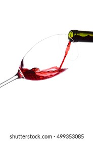 Pouring red wine from bottle to glass isolated on white background