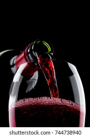 Pouring red wine from bottle to glass isolated on black background
