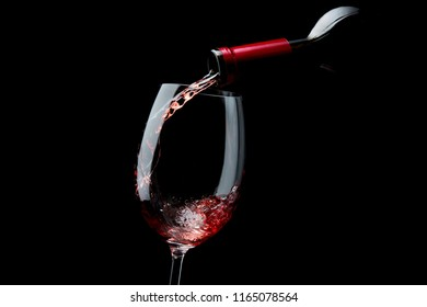 Pouring red wine from bottle into the glass on black background