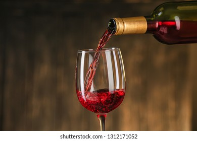 Pouring of red wine from bottle into glass on dark background